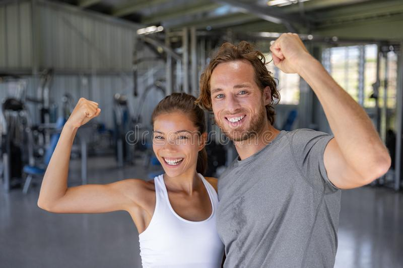 Fit power couple happy flexing strong arms showing off success training at fitness gym - Smiling Asian woman stock image