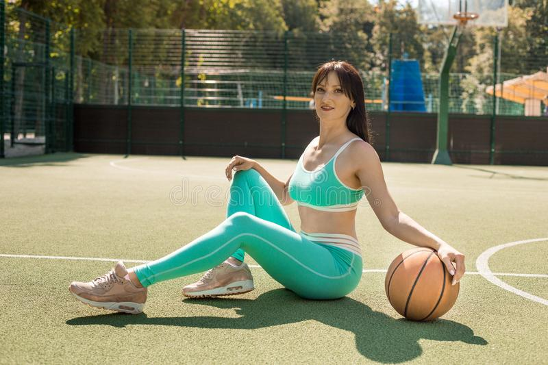 Fit pretty girl sitting on the floor with basketball on sport playground stock photo