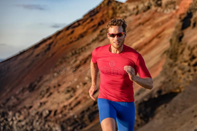 Fit runner man sport athlete trail, running outside on volcano mountain in desert. Motivation and focus during exercise. Fitness. And health stock photography