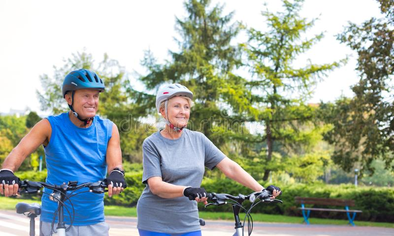 Fit senior couple walking with bicycle in park stock photography