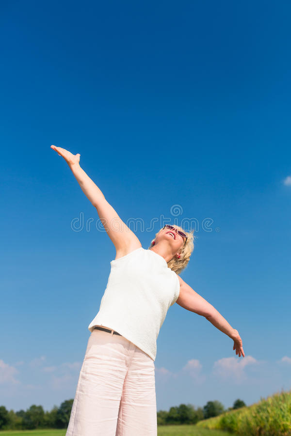 Fit senior woman looking up to the sky while enjoying retirement. Low-angle view of a fit senior woman looking up to the sky with outstreched arms while enjoying royalty free stock image