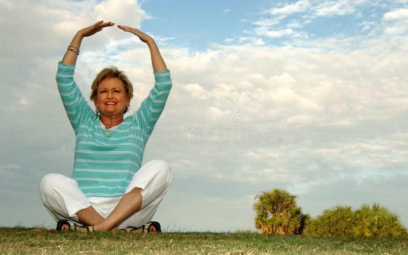 Fit senior woman meditation/praise. A fit senior woman sitting on a hill in a meditation/praise pose stock photo