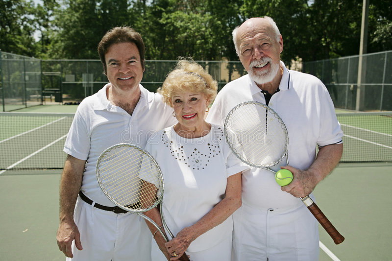 Fit Seniors With Tennis Pro. Active, fit senior couple who play tennis, posing with their instructor