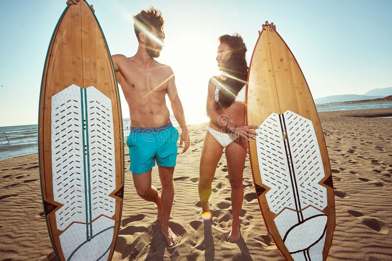 Fit, sexy couple, talking on a beach, holding surfboards. ultraviolet radiation, protection concept stock images