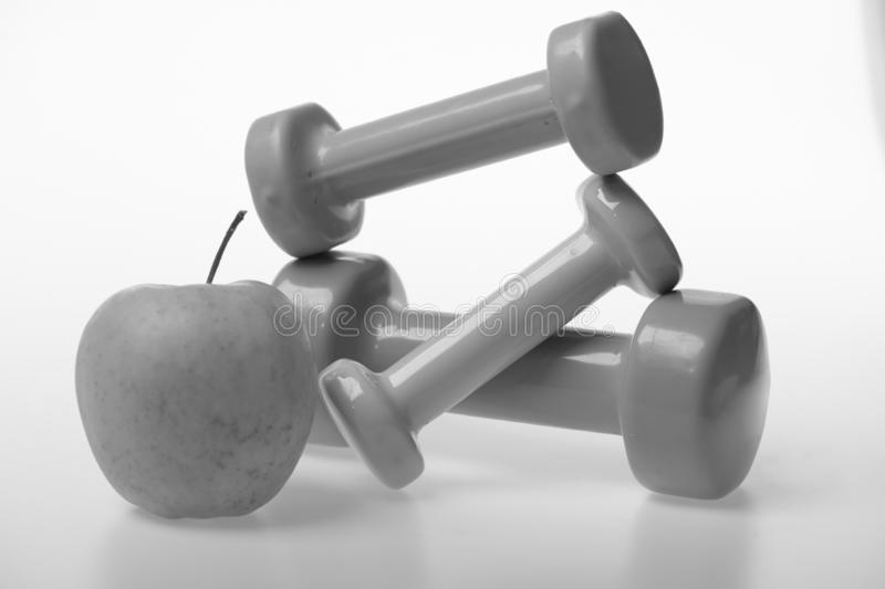 Apple fruit and pink, green and blue barbells stock photos