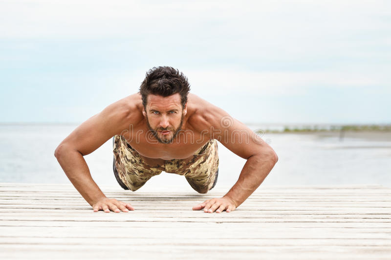 Fit shirtless male fitness model in push up exercise stock photography