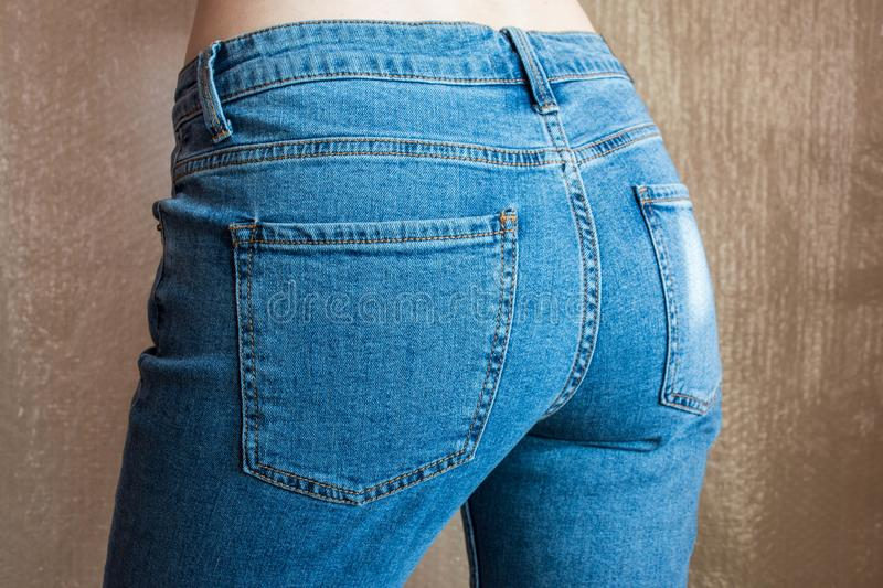 Fit slim female in blue jeans. Woman buttocks in denim. royalty free stock photo