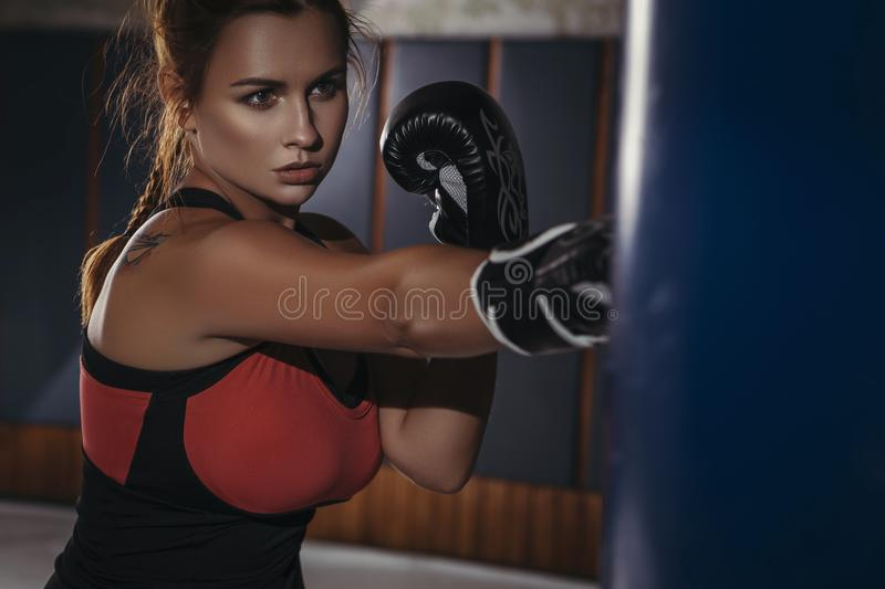 Fit slim young beautiful brunette woman boxing in sportswear. Da. Rk dim light. Toned image royalty free stock photo