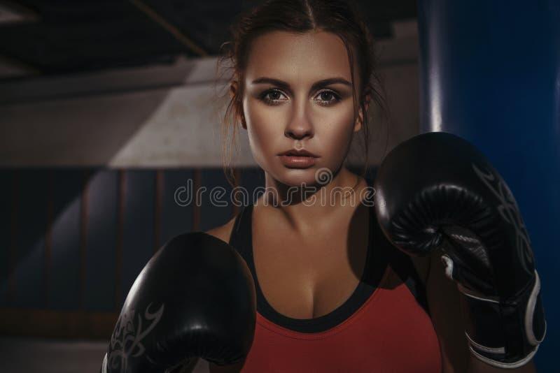 Fit slim young beautiful brunette woman boxing in sportswear. Da. Rk dim light. Toned image stock image