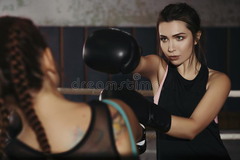 Fit slim young beautiful brunette women boxing in sportswear. Da. Rk dim light. Toned image stock image