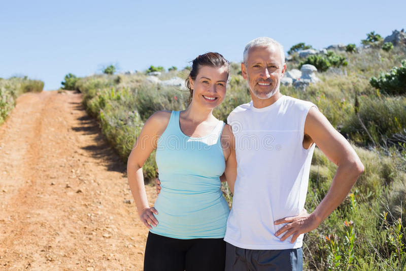 Fit smiling couple embracing and smiling at camera on country trail. On a sunny day royalty free stock image
