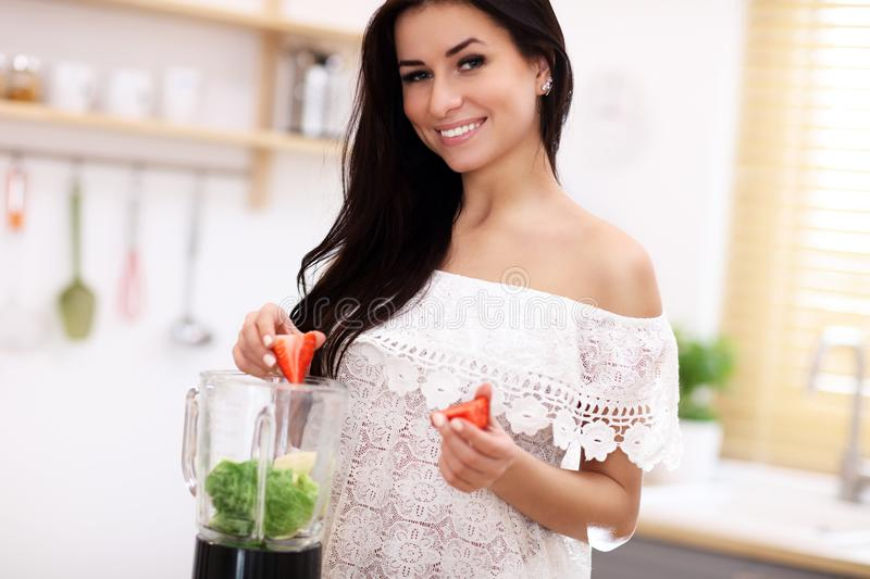 Fit smiling young woman preparing healthy smoothie in modern kitchen royalty free stock images