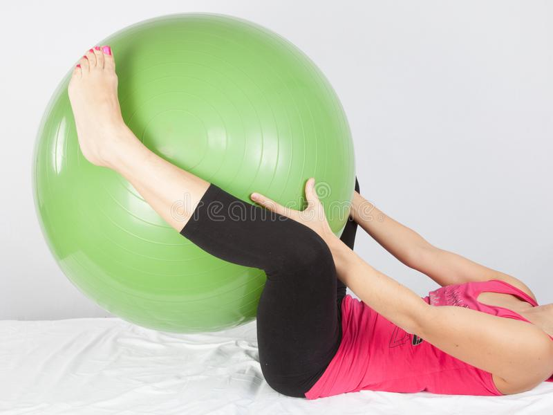 Sport girl lying with large fitness green ball make woman exercice. Fit sport girl lying with large fitness green ball make woman exercice stock photo