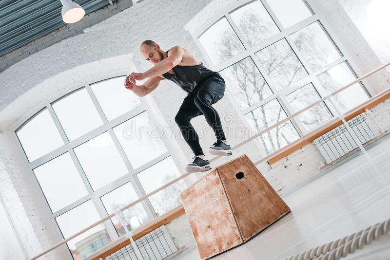 Strong male athlete jumping at box in workout hall. Fit sportsman doing jump exercises on wooden box in cross workout gym. Strong male athlete jumping at box in royalty free stock photo