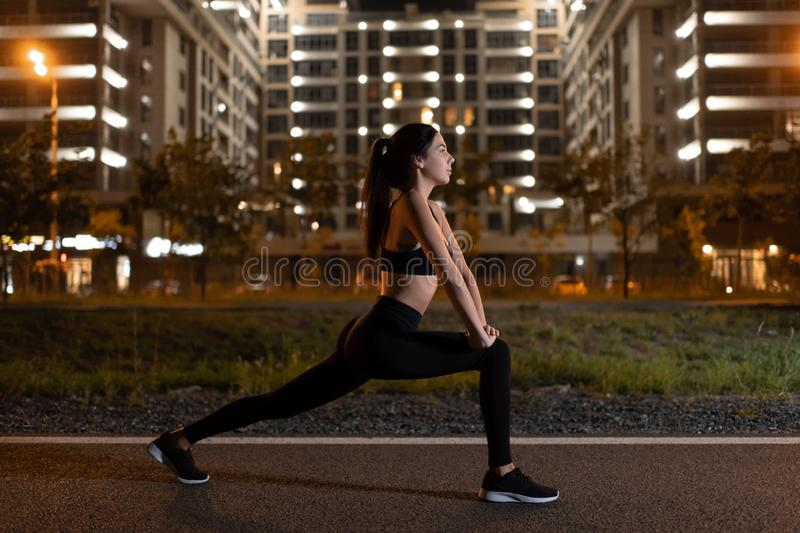 Fit sportswoman stretching legs during night workout. Side view of athletic young woman in sportswear practicing lunge exercises while training at night on urban stock photography