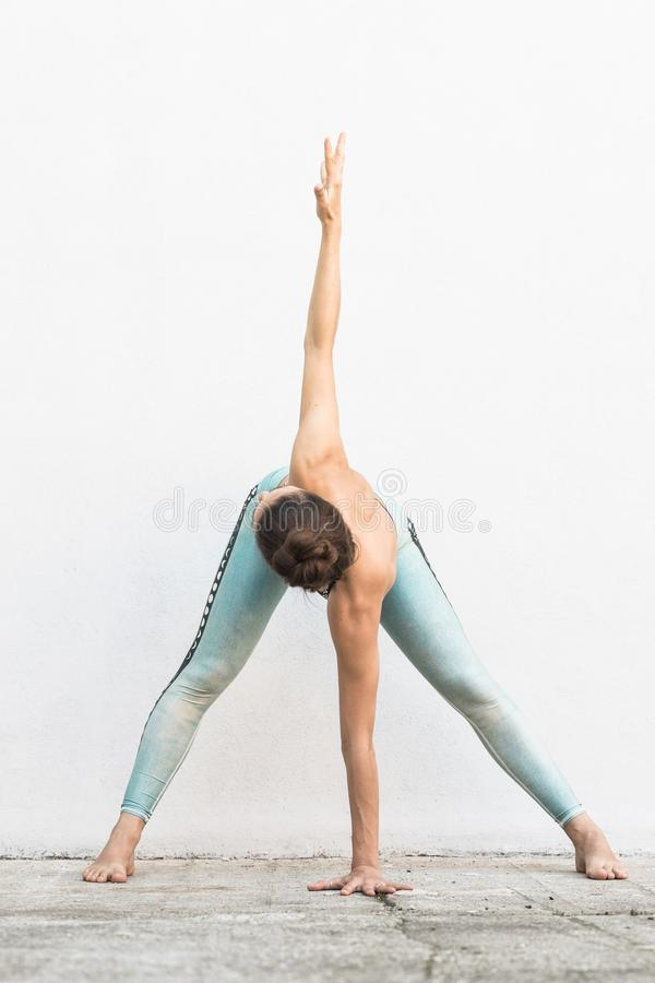 Fit sporty active girl in fashion sportswear doing yoga fitness exercise in front of gray wall, outdoor sports, urban stock photos