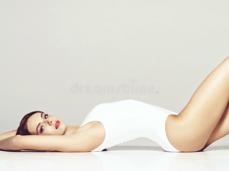 Fit and sporty girl in underwear. Beautiful and healthy woman po. Sporty fashion model posing in white slimming underwear. Fit and girl in studio royalty free stock photo