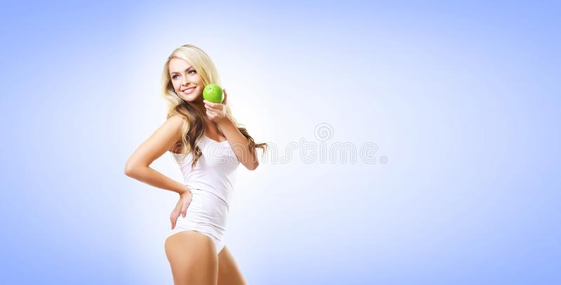 Fit and sporty girl in white underwear. Beautiful and healthy woman eating green apple over blue background. Sport, fitness, diet royalty free stock photography