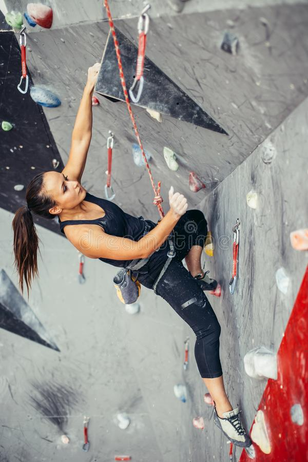 Fit sporty student girl moving up at rock climbing wall at the gym royalty free stock image