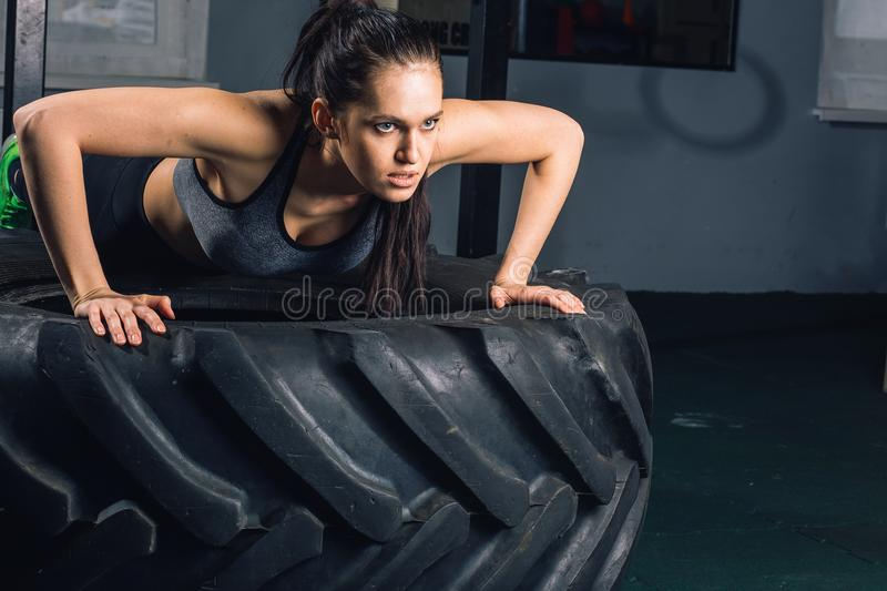 Fit sporty woman doing push ups on tire strength power training concept stock images