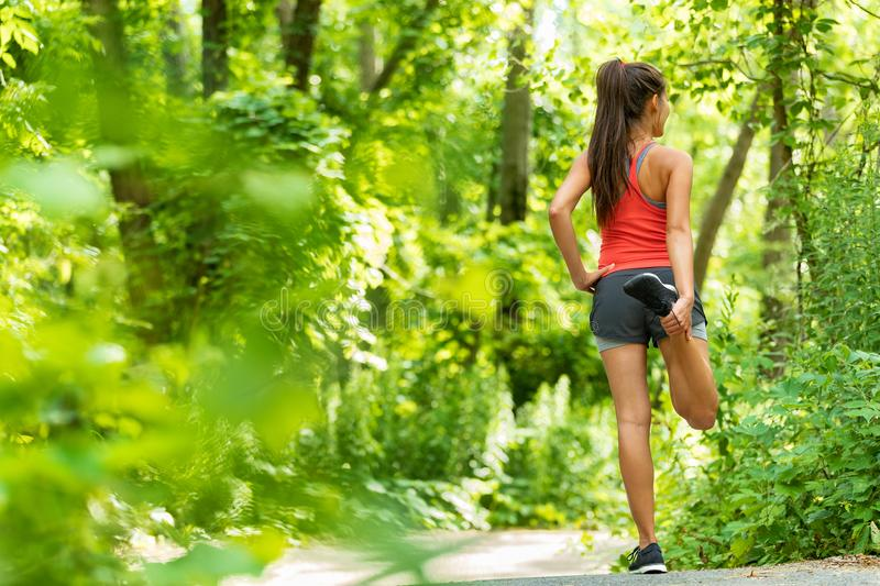 Fit stretch woman stretching quad leg muscle standing getting ready to run jogging outside in summer nature forest park green royalty free stock photo
