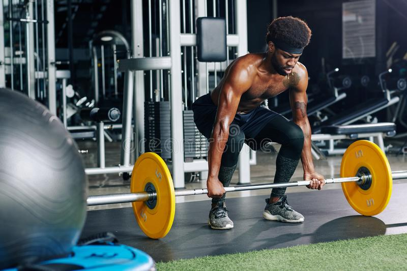 Sportsman working out with heavy weight stock images