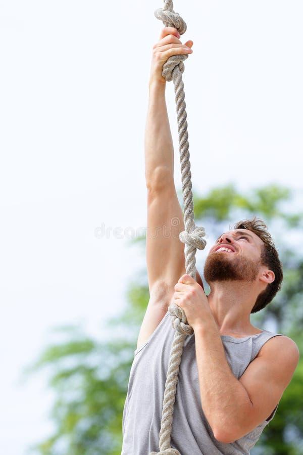 Fit strong man cross training climbing rope stock photos