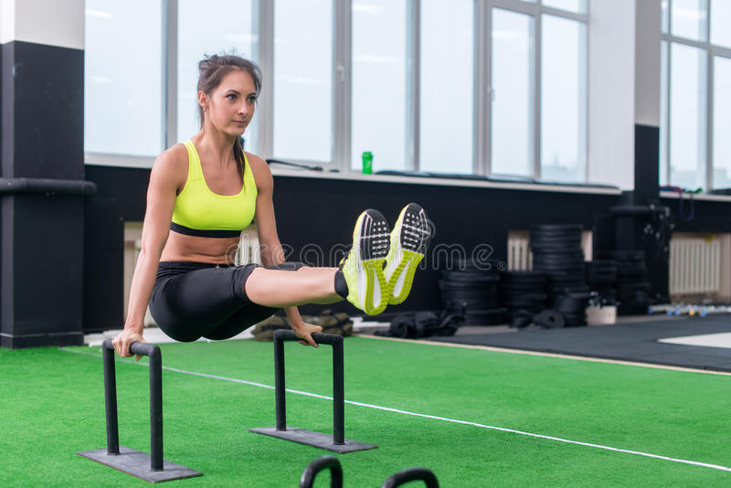 Fit strong woman doing L-sits work-out in gym, lifting up her legs, using parallel bars stock image