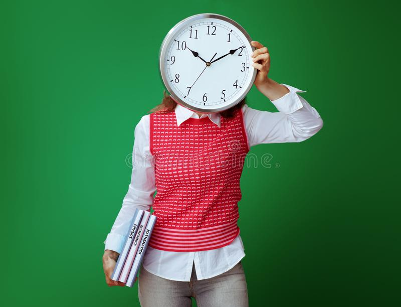 Fit student with textbooks hiding behind white round clock royalty free stock photo