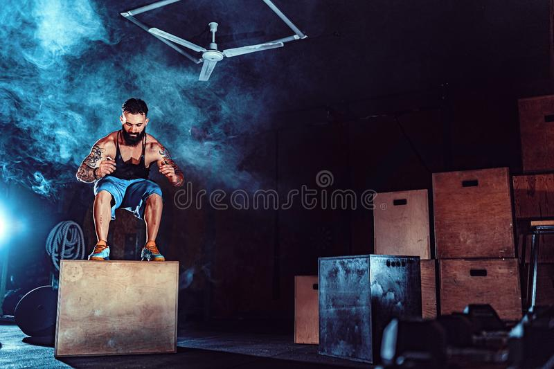 Fit tattoed bearded man jumping onto a box as part of exercise routine. Man doing box jump in the gym. Athlete is stock images