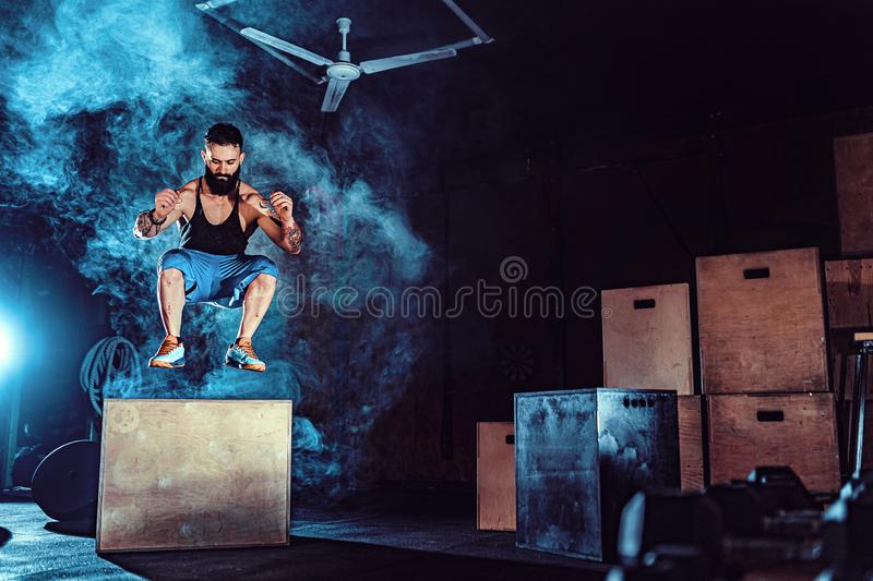 Fit tattoed bearded man jumping onto a box as part of exercise routine. Man doing box jump in the gym. Athlete is. Performing box jumps royalty free stock image