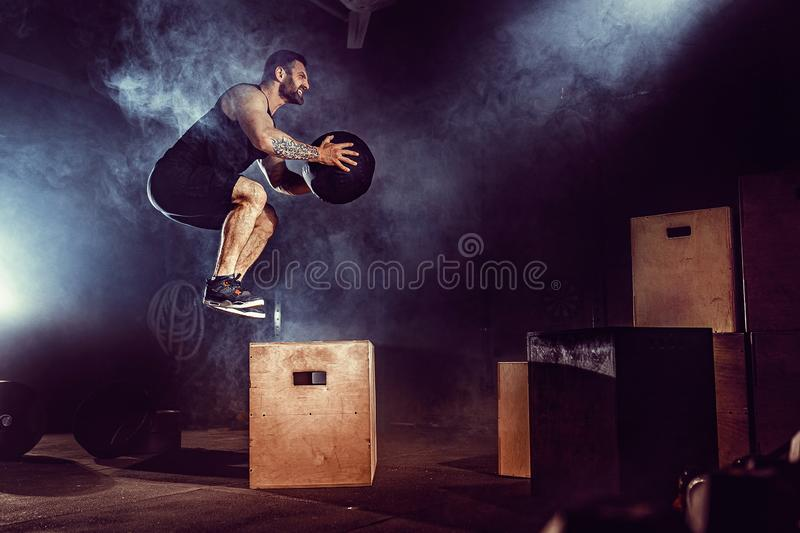 Fit tattoed bearded man jumping onto a box as part of exercise routine. Man doing box jump in the gym. Athlete is. Performing box jumps stock photo