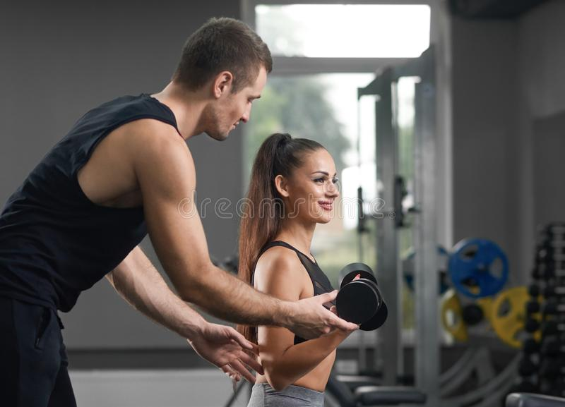 Fit trainer helping and supporting energetic sporty girl. royalty free stock photos