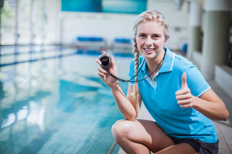 Fit trainer showing stopwatch with thumbs up. At the pool royalty free stock photography
