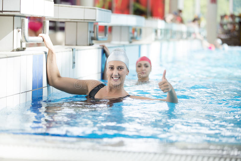Fit trainer showing stopwatch with thumbs up at the pool royalty free stock photography