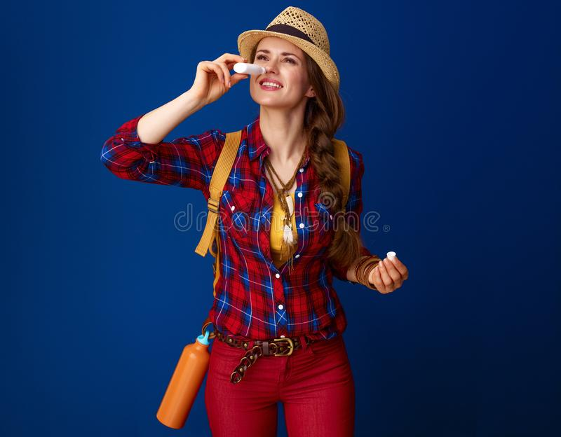 Fit traveller woman isolated on blue using nasal drops. Searching for inspiring places. fit traveller woman in a plaid shirt using nasal drops isolated on blue stock images