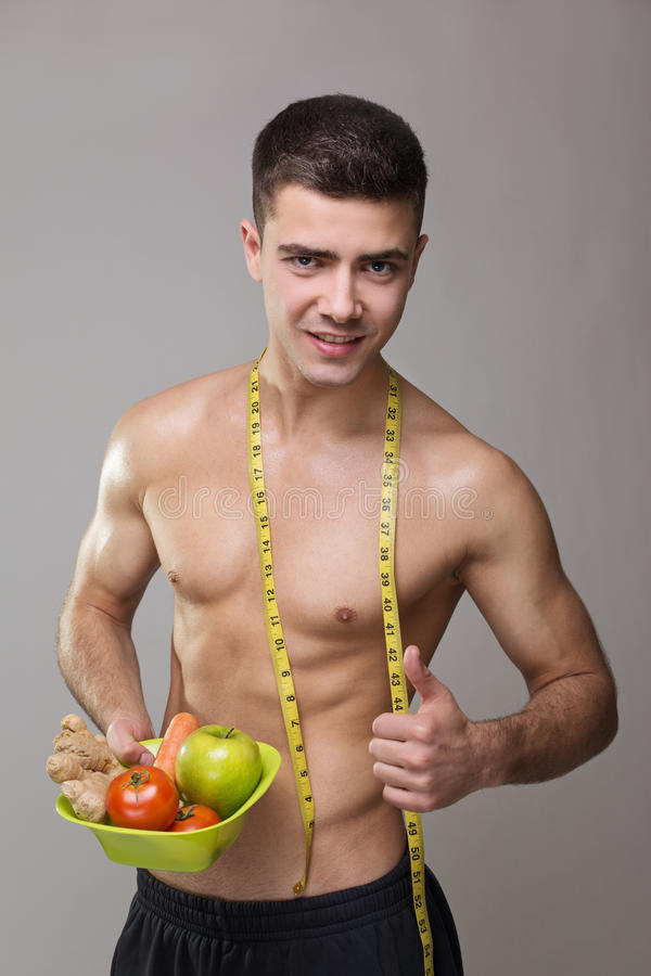 Fit vegan man with measuring tape and healthy food. Fit vegan young Caucasian man with measuring tape smiling showing thumb up and holding a healthy food bowl stock photos