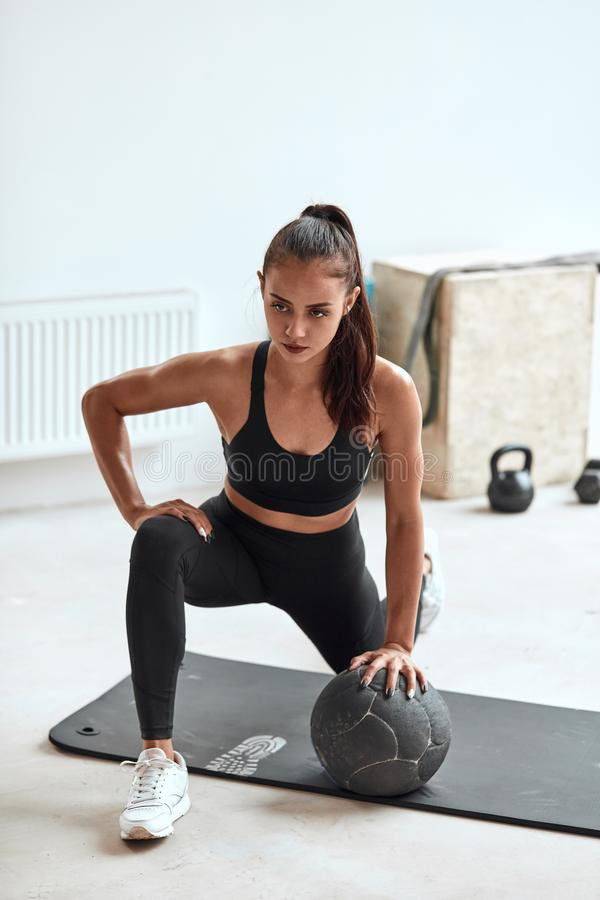 Fit well-trained girl in black wear with medball. Fit pretty woman in sportswear sit exercising, stretching leg with medball. Light gym background royalty free stock photo