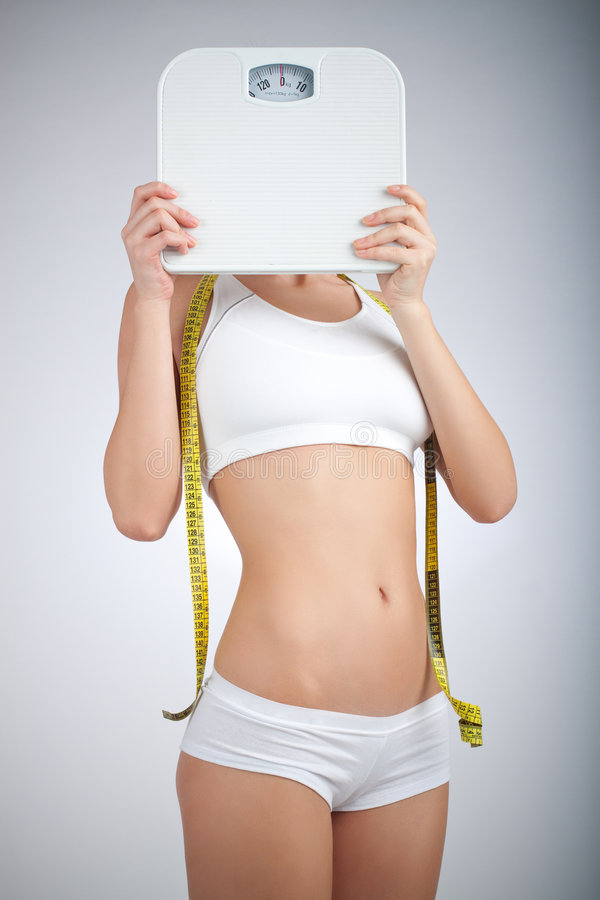 Fit Woman. Woman with bathroom scale and measuring tape stock images