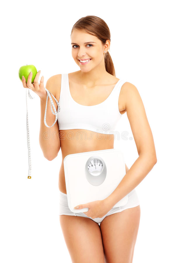 Fit woman with apple tape and scales. A picture of a fit woman with apple tape measure and bathroom scales royalty free stock photos