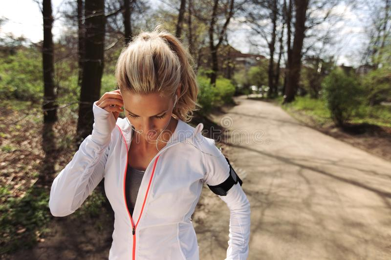 Fit woman athlete before her run in forest. Image of pretty young blonde wearing earphones to listen music before starting her running workout. Fit female royalty free stock photography