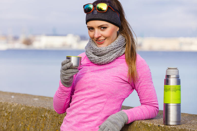 Fit woman in cold day warming up drink tea royalty free stock image