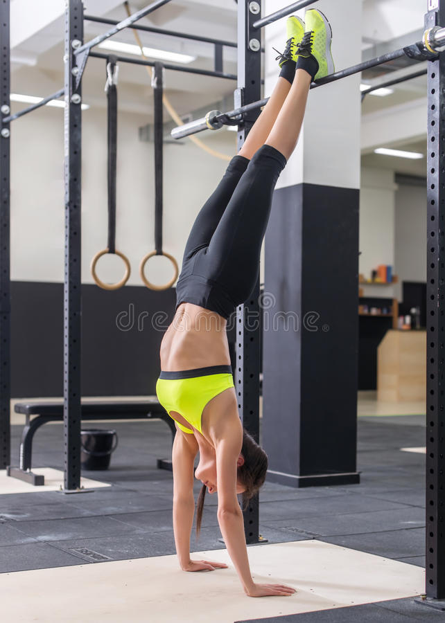Fit woman doing handstand Athlete standing on hands Concept balance sport fitness. stock photography