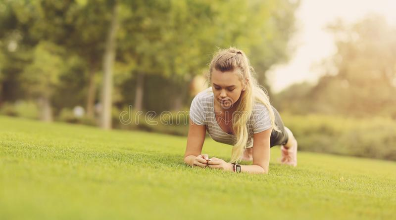 Fit woman doing plank exercise outdoor in the park on the green grass in the morning - Healthy lifestyle, Endurance and motivation. Concept - Copy space stock photography