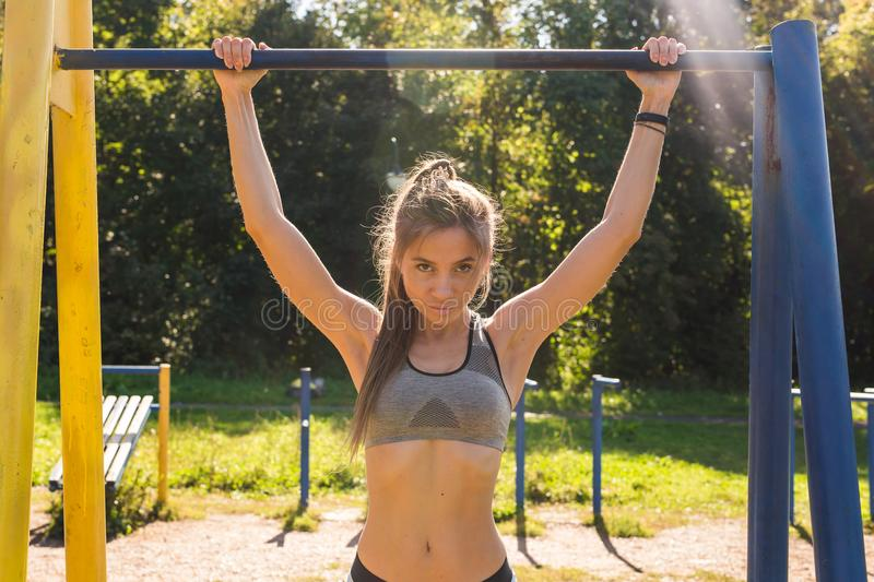 Fit woman doing pull-ups. Young athletic fitness woman working out at outdoor gym doing pull ups at sunrise stock photos