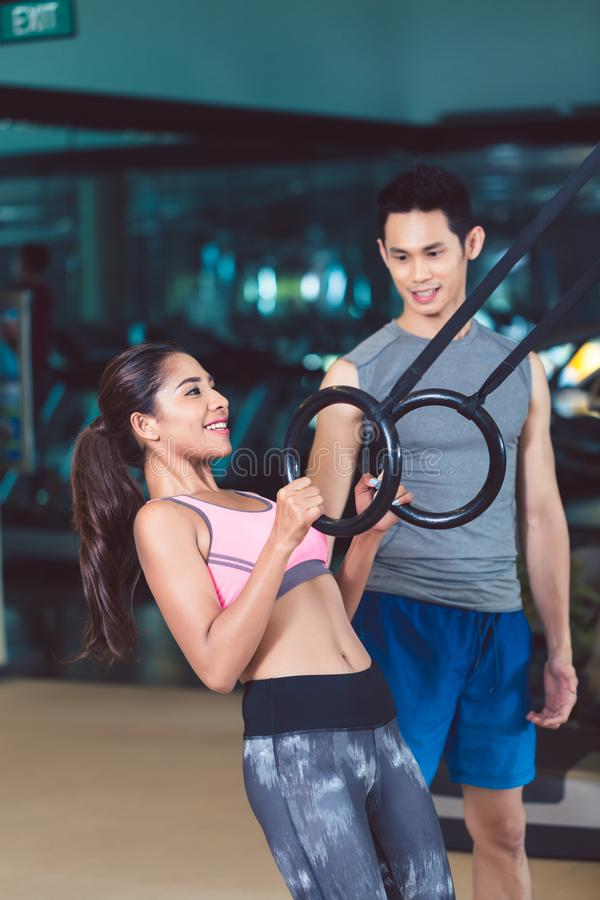 Fit woman doing ring biceps curl exercise during training. Side view of a fit and cheerful young women doing ring biceps curl exercise during workout with a stock image