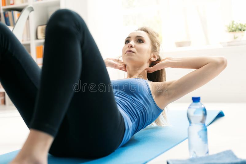 Fit woman doing sit ups at home on the floor. Young fit woman doing sit ups and exercising on the floor at home in the living room, fitness and sports concept royalty free stock photos