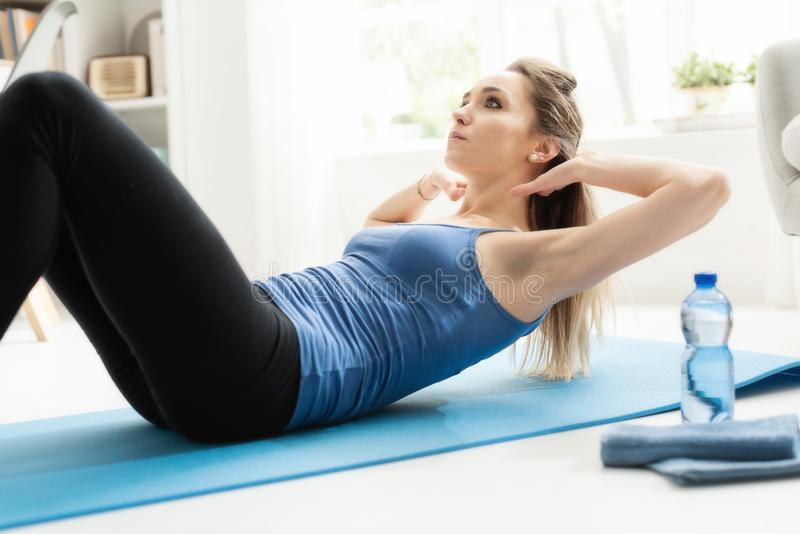 Fit woman doing sit ups at home on the floor royalty free stock images