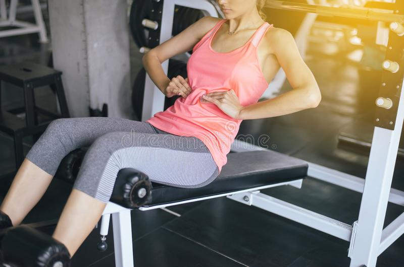 Fit woman doing situp or crunches in gym,Female exercise muscular her stomach royalty free stock image