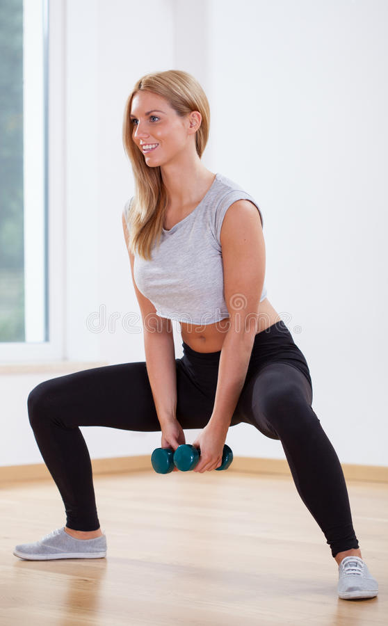 Fit woman doing squat. Fit beauty woman doing squat with dumbbell royalty free stock photography